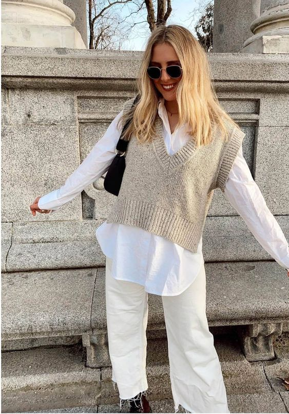 a pretty neutral fall look with an overiszed white shirt, a creamy knit vest, white jeans, black combat boots and a small bag