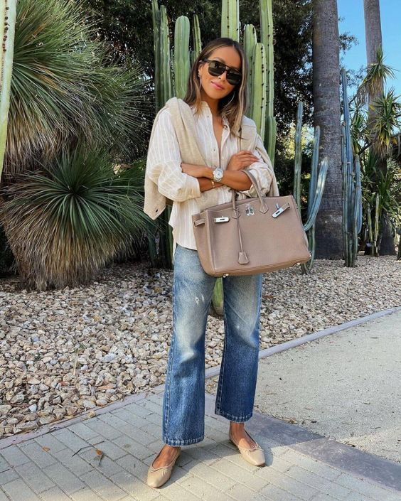 a striped shirt, blue jeans, a neutral jumper, tan flats and a tan bag for a cool summer to fall look