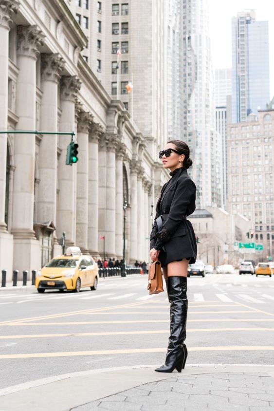 a black blazer dress paired with a black turtleneck, a black belt and knee high slouchy boots plus a brown bag for a sexy look