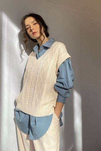 white jeans, an oversized blue shirt and a white cable knit vest is a fall outfit suitable for work