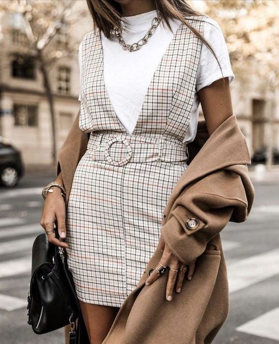 a white t-shirt, a creamy plaid mini overall, a chain necklace, a black bag and a tan coat for a lovely fall look