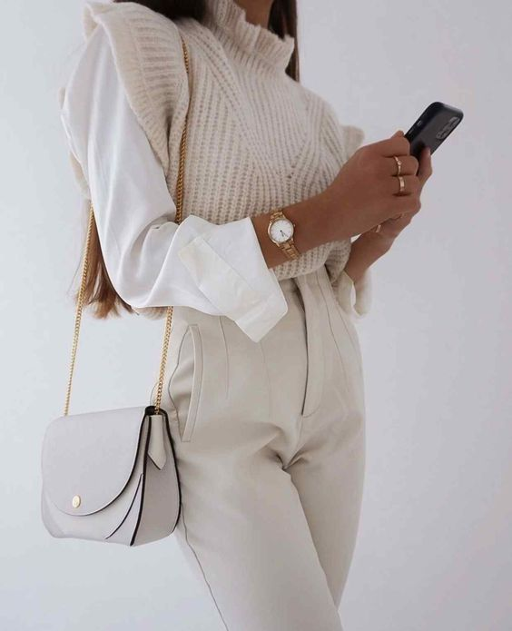 white high waisted pants, a white shirt, a creamy knit vest with ruffles and a dove grey bag for a neutral fall look