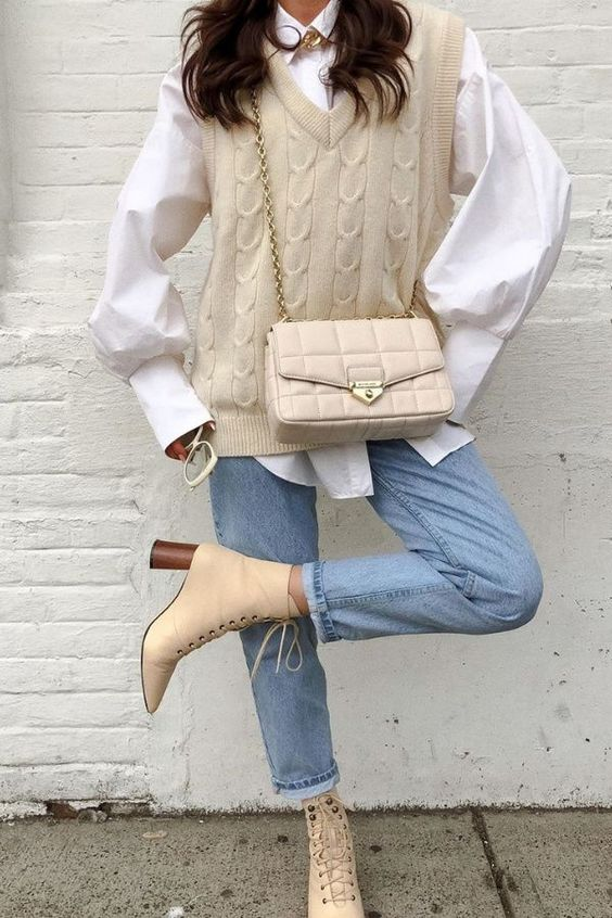 a pretty fall outfit with an oversized white shirt, a creamy braided knit vest, light blue jeans, tan heeled boots and a creamy bag