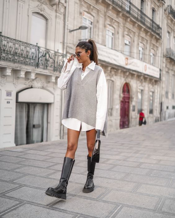 a white shirtdress, an oversized grey waistcoat, black knee high boots and a black bag for a super trendy and edgy look