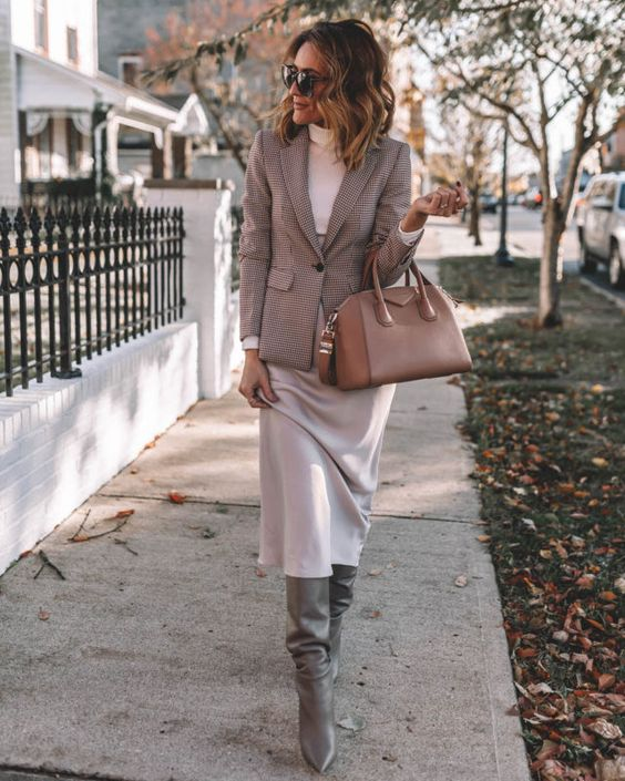 an elegant work look with a white turtleneck, a neutral midi skirt, grey slouchy boots, a plaid blazer and a tan bag