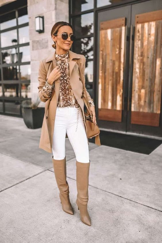 a snakeskin print turtleneck, white skinnies, tan slouchy boots, a tan short trench and a tan bag for a casual look