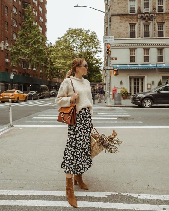 a fall outfit with a neutral sweater, a black printed midi skirt, rust suede booties and a rust-colored bag