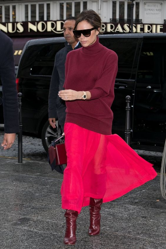 an oversized burgundy turtleneck sweater, a hot pink midi skirt, burgundy slouchy boots and a bag by Victoria Beckham