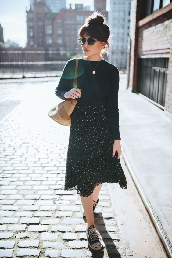 a black jumper, a coin necklace, a black polka dot midi skirt, black sneakers and a straw bag for a Parisian look
