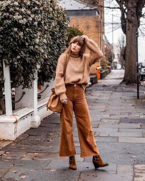 a fall-colored outfit with a tan sweater, rust-colored flare trousers, rust-colored suede boots and a tan bag