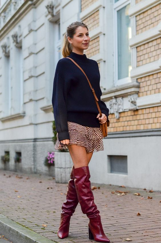 a pretty outfit with a navy sweater, a ruffle printed mini, fuchsia slouchy knee boots and a tan bag