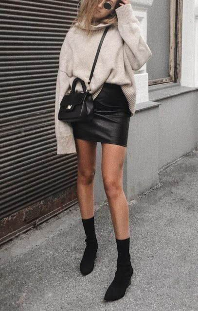 a simple and stylish look with a black leather mini, black sock boots, a grye oversized sweater and a black bag