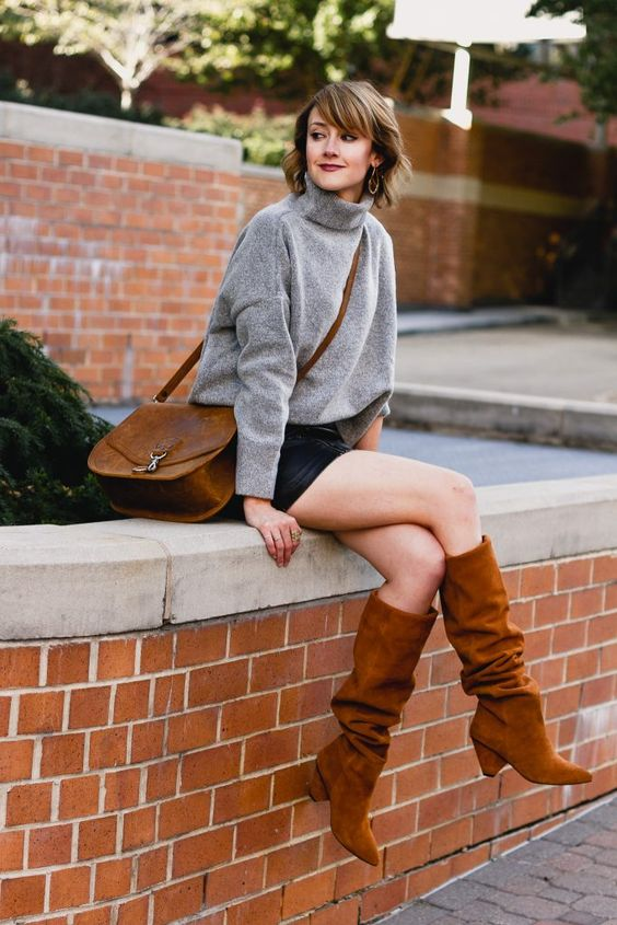 a timeless fall look with a grey turtleneck sweater, a black leather mini, rust-colored slouchy boots and a brown bag