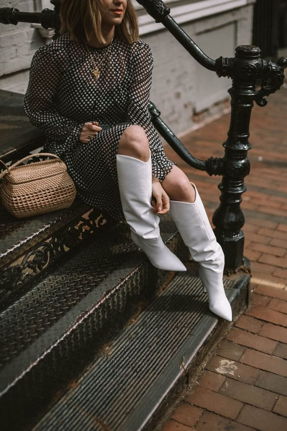 a black and white polka dot midi dress with long sleeves, white slouchy boots and a basket-style bag