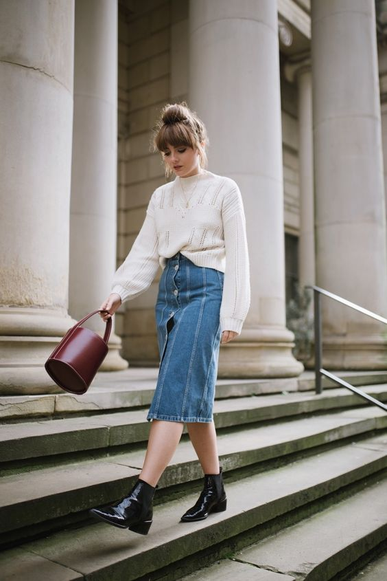 a fall boho look with a white jumper, a blue midi denim skirt, black lacquer booties and a burgundy bucket bag