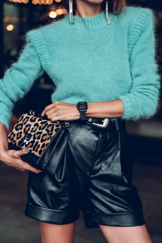 a light green sweater, black leather shorts, a black belt, a leopard print mini bag and statement earrings