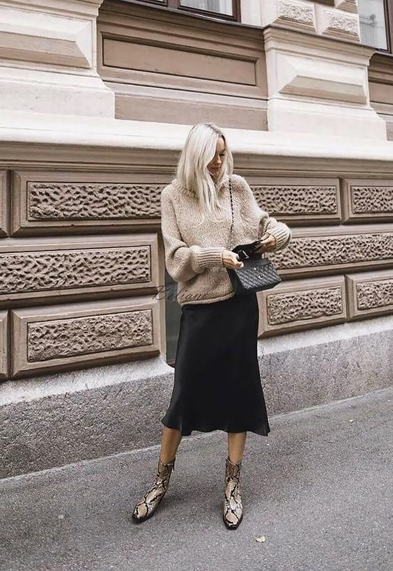 a fall look with a tan oversized sweater, a black slip midi skirt, snakeskin print booties and a black bag