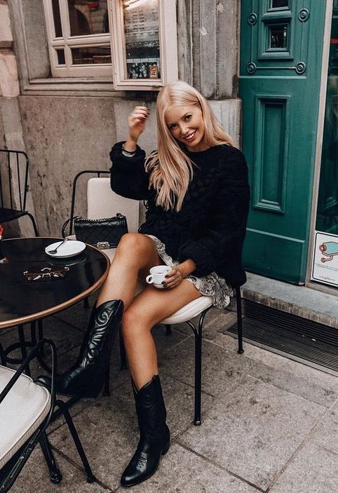 a black oversized sweater, a ruffle mini skirt, black cowboy boots and a black bag for a chic and girlish fall look