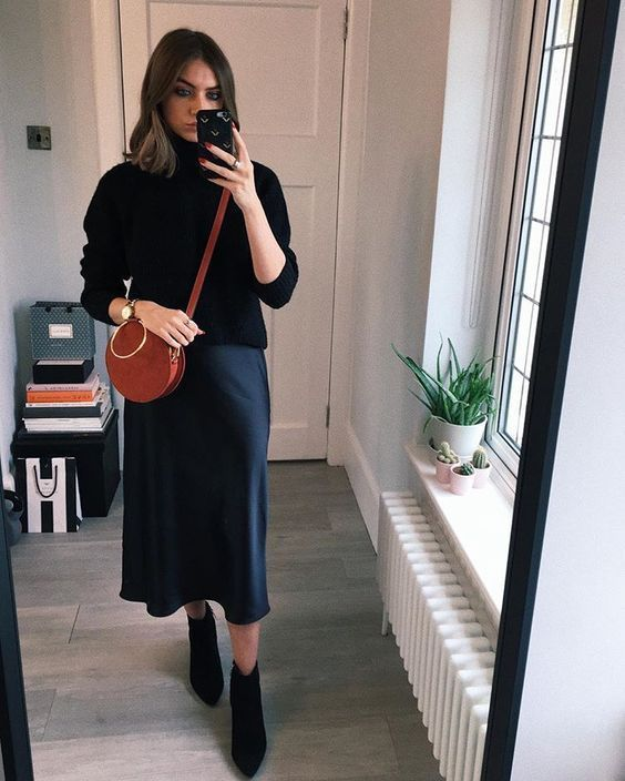 a refined outfit with a black turtleneck, a navy slip midi skirt, black boots and a round red bag is cool