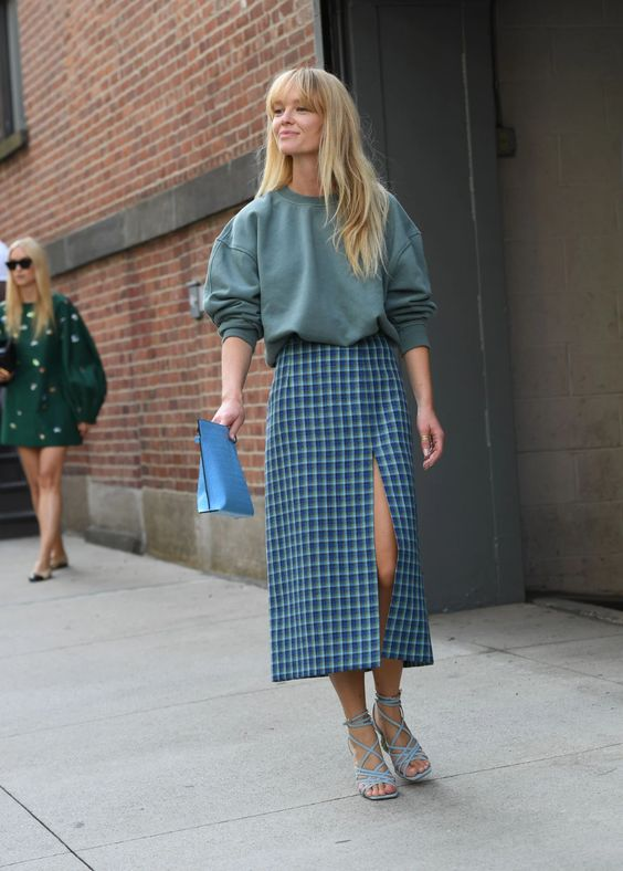 an oversized olive green sweatshirt, a blue plaid midi skirt wiht a front slit, blue lace up shoes and a blue clutch