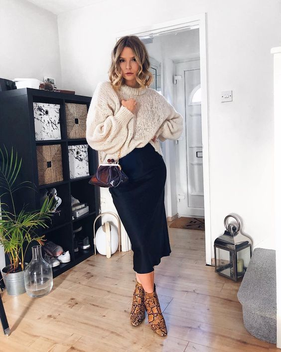 a chic fall outfit with a black slip midi skirt, a neutral oversized sweater, brown snakeskin print booties and a red vintage bag