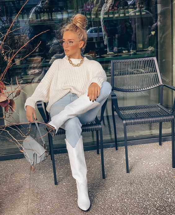 a white chunky knit jumper, light blue jeans, white cowboy boots, a light blue bag and a chunky chain necklace