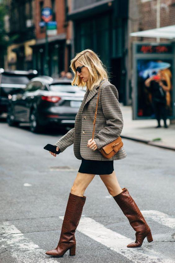 an oversized grey blazer, black mini skirt, brown reptile leather bootis and a tan mini crossbody bag