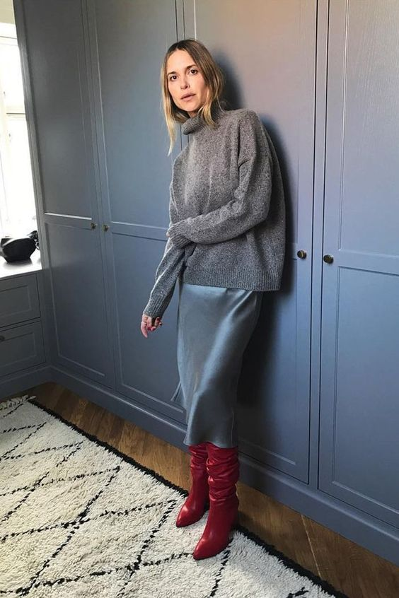 a beautiful fall look with an oversized grey sweater, a blue slip midi, deep red boots is gorgeous