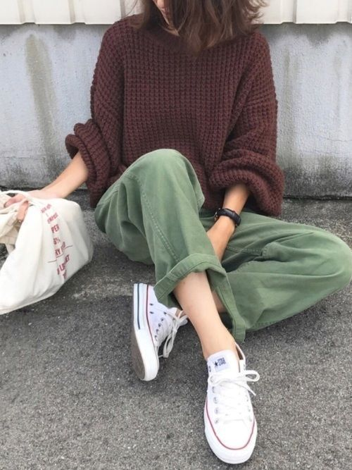 a brown chunky knit oversized sweater, green wide leg jeans, white sneakers and a white tote