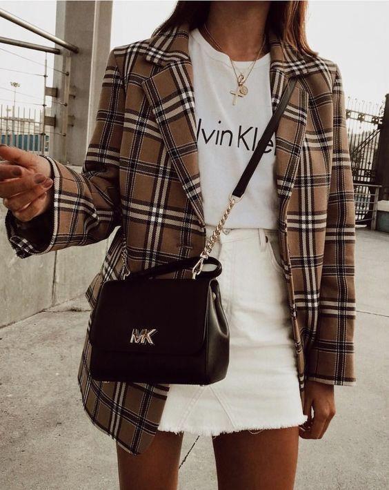 a white printed t-shirt, a white denim mini skirt, a tan plaid oversized blazer, a black bag for an easy fall look