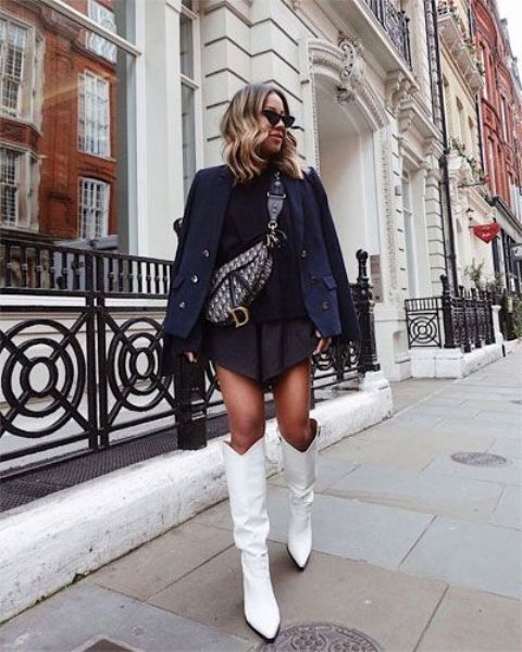 a stylish fall outfit with a black top and asymmetrical mini pleated skirt, a navy cropped coat, a printed bag and cowboy boots