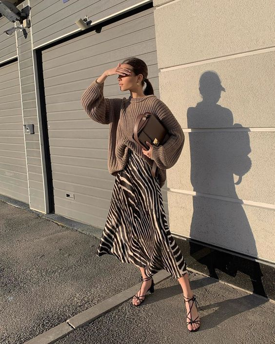 a taupe chunky sweater, a zebra print midi slip skirt, black heels and a taupe bag for a refined look