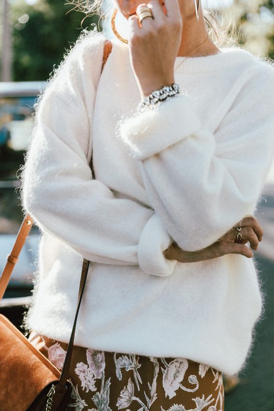 a white oversized fuzzy sweater, a rust-colored printed skirt and a rust-colored bag plus statement earrings