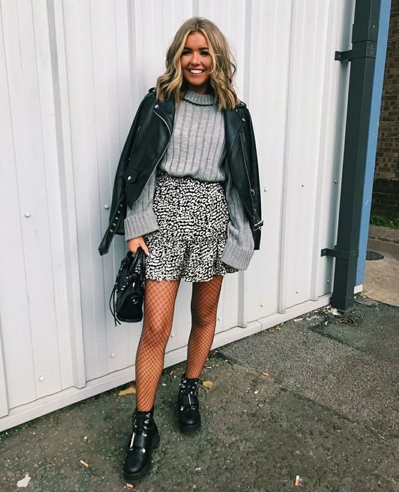 a grey ribbed long sleeve top, a printed mini skirt, black tights, black boots, a black leather jacket and a bag