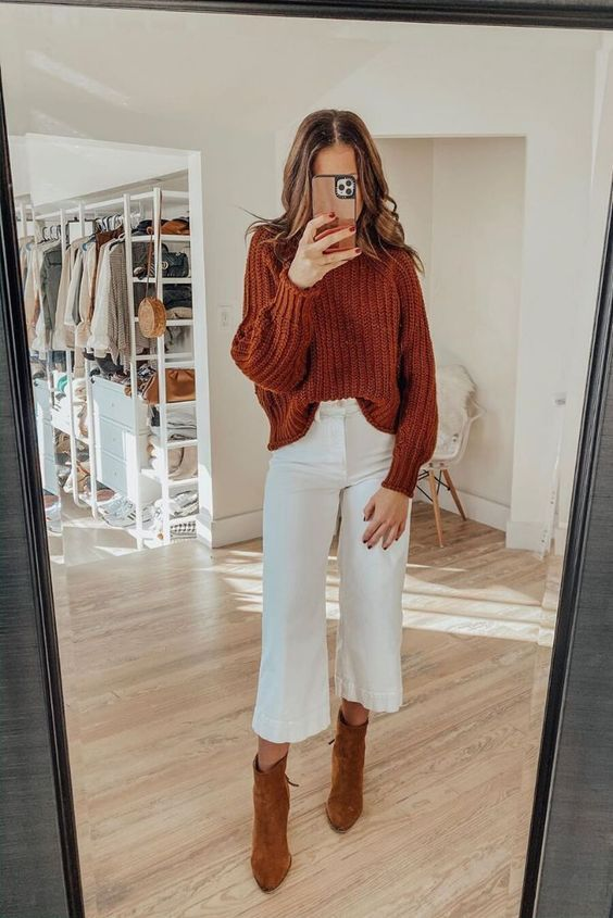 a rust-colored chunky turtleneck sweater, white cropped jeans, rust suede boots for a bold fall look