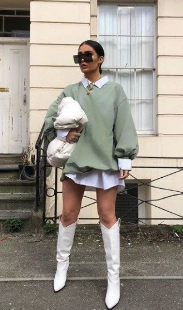 a white shirtdress, an olive green oversized sweatshirt, white cowboy boots, a white padded clutch and statement necklaces