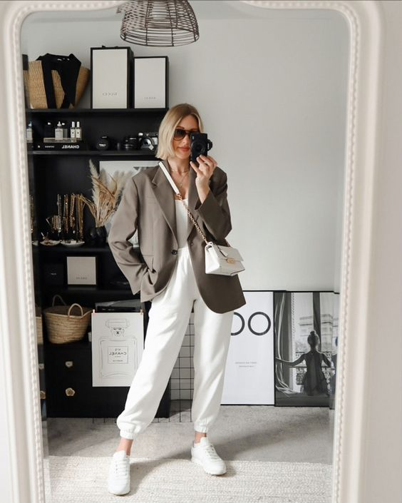 a white top, white joggers, white sneakers, an oversized grey blazer and a white mini bag for a comfy fall look