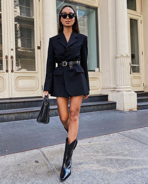 a refined total black look with a blazer dress, a belt, a bag and cowboy boots is an ultimate solution to rock this fall