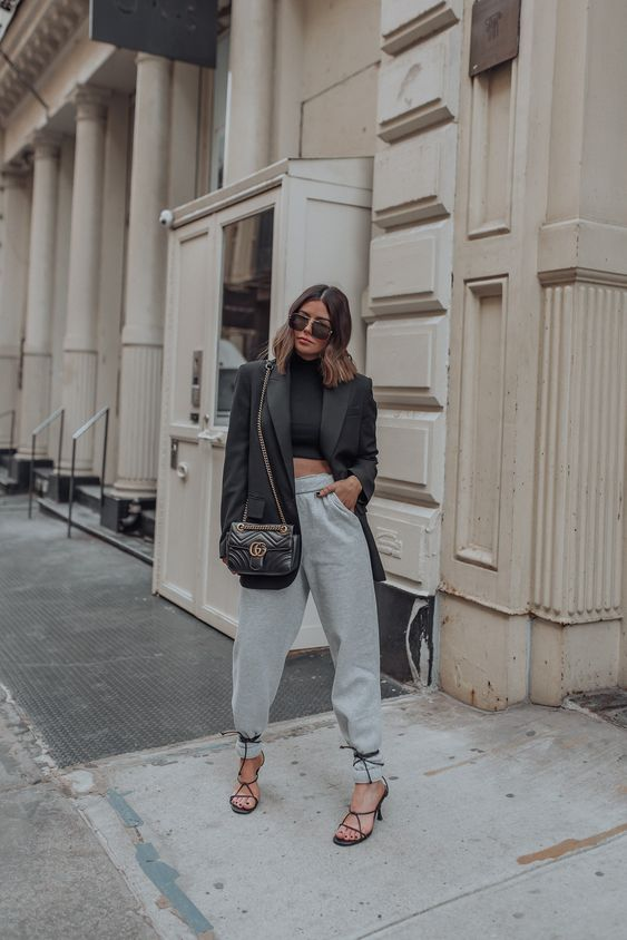 an edgy work look with a black crop top, grey sweatpants, black lace up heels, a black oversized blazer and a black bag