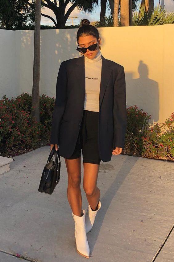 Kendall Jenner wearing a white turtleneck, black biker shorts, an oversized navy blazer, a black bag and white cowboy boots
