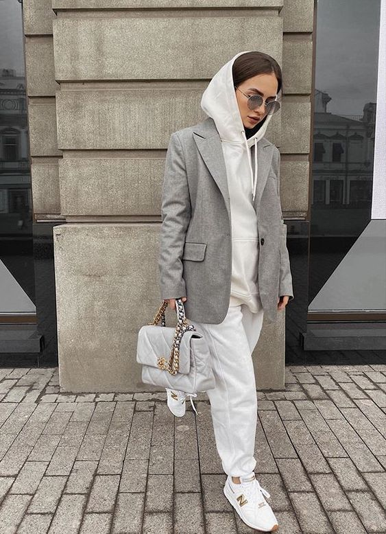 a comfortable fall outfit with white sweatpants, a white hoodie, a grey blazer, white sneakers and a white bag with chain