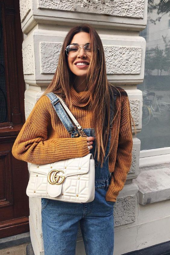 a rust-colored chunky sweater, a blue denim overall, a creamy bag for a cozy fall look