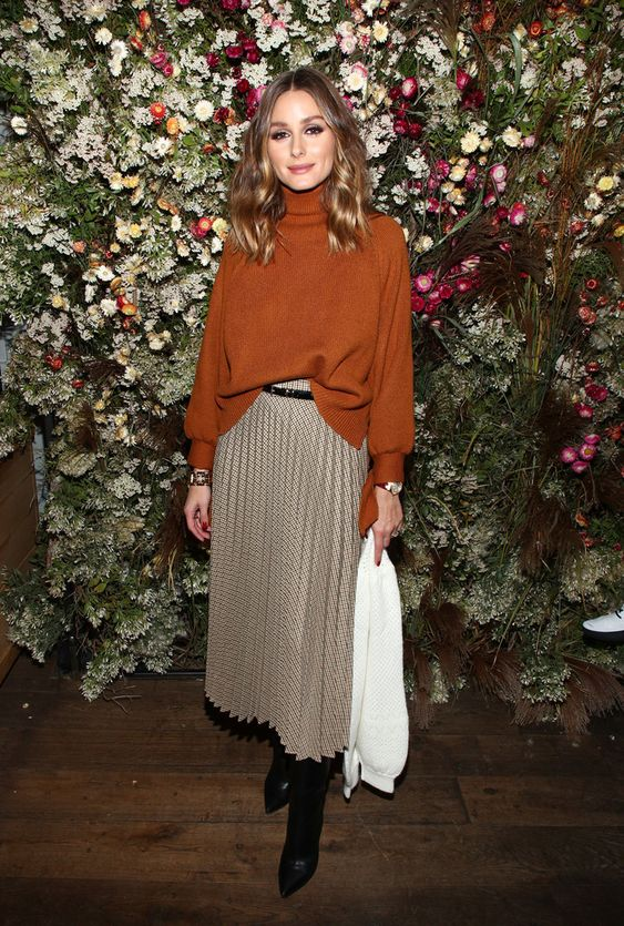 a rust-colored oversized turtleneck, a neutral plaid midi skirt, black boots and a black belt for the fall