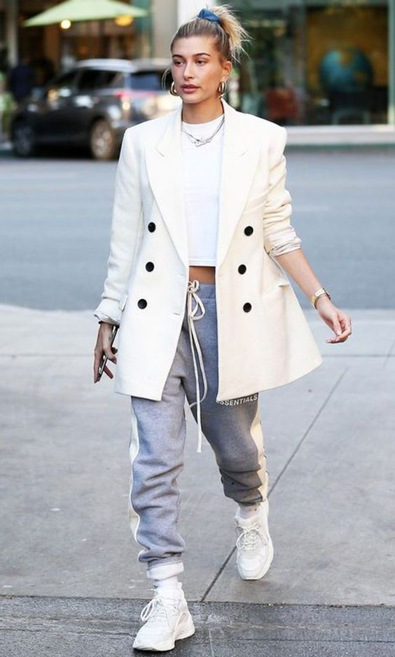 Hailey Bieber wearing a white crop top, a creamy oversized blazer, grey sweatpants, white trainers for a comfy look