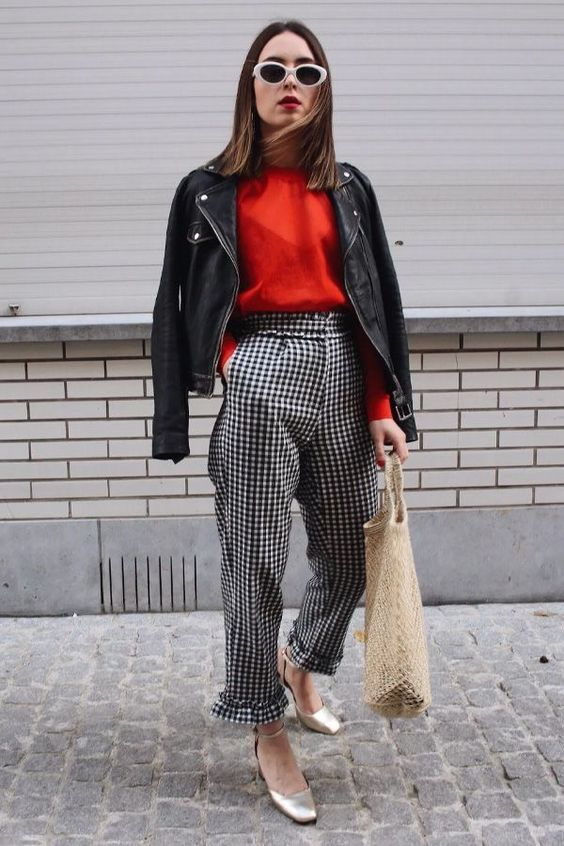 a Parisian chic look with a red top, plaid high waisted trousers, a black leather jacket, silver ankle strap shoes and a tote