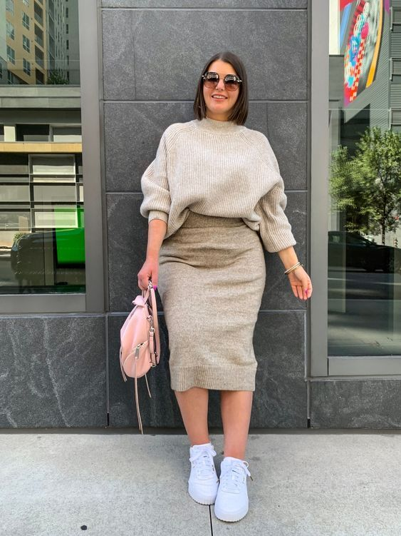 a neutral fall look with a grey turtleneck sweater and a knit midi skirt, white sneakers and a pink backpack