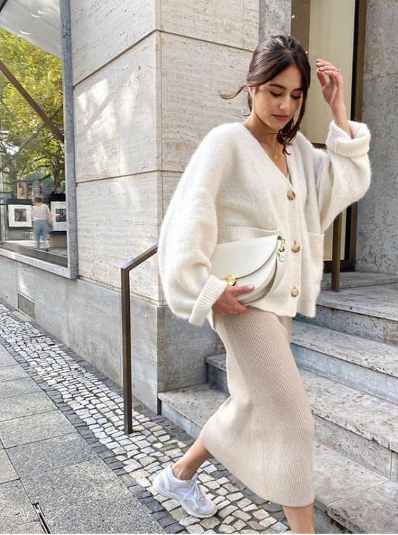 a pretty creamy fall outfit with a neutral midi skirt, a white oversized cardigan, grey trainers and a white bag