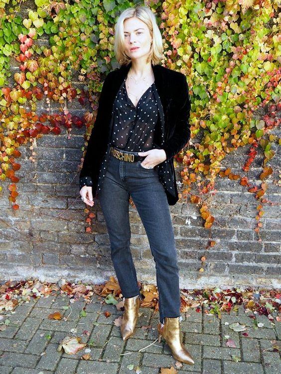 a black polka dot shirt, a black velvet blazer, grey jeans, a logo belt and gold boots for a chic look
