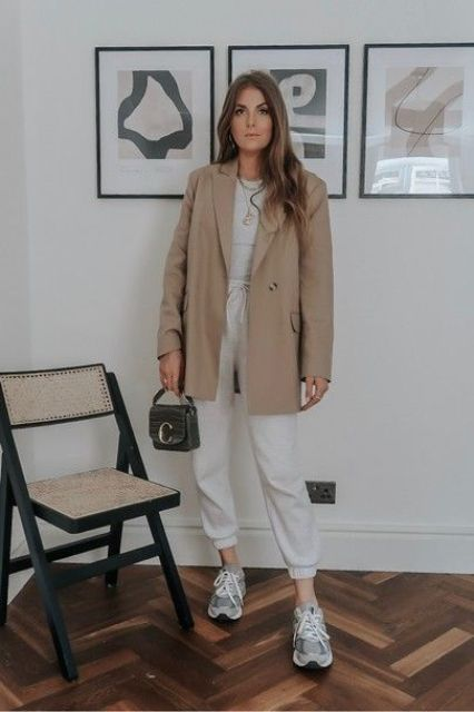 a grey top, white sweatpants, grey trainers, an oversized tan blazer and a grey mini bag to rock this fall