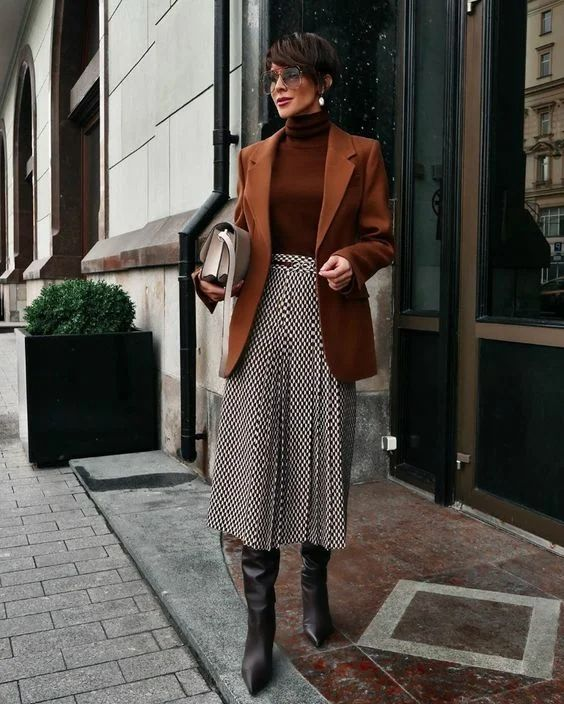 a refined fall outfit suitable for work - a brown turtleneck, a rust-colored oversized blazer, a printed pleated midi skirt, black boots and a white bag